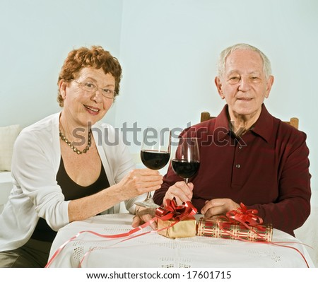 senior couple having wine and exchanging gifts - stock photo