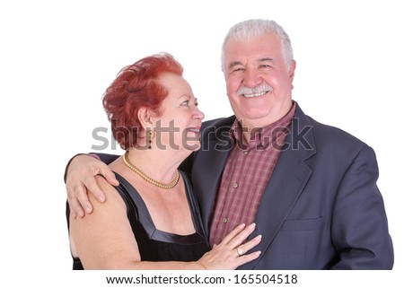 Senior couple, he is looking at you while she is proudly looking at him - stock photo