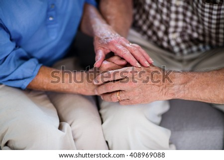 Senior couple holding hand at home