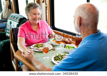 Senior couple holding hands about to eat a healthy meal in their motor home. - stock photo