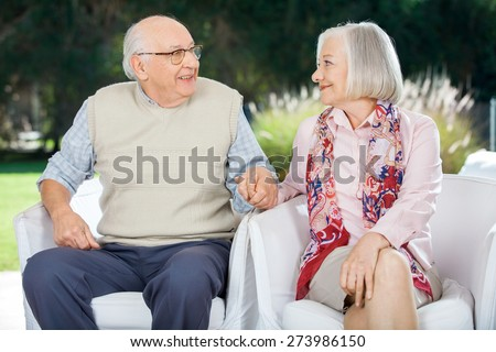 Senior couple holding hands and looking at each other while sitting on chairs at nursing home porch - stock photo