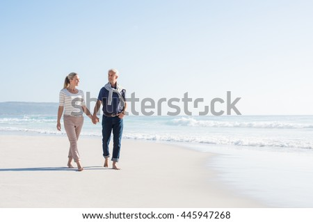 Senior couple holding hands at the beach on a sunny day. Mature couple in love holding hands and looking each other at the seaside. Smiling wife and happy husband walking barefoot on the white sand. - stock photo