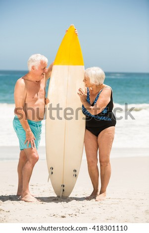 Senior couple holding surfboard on a sunny day - stock photo