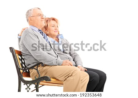Senior couple hugging and looking in the distance seated on a bench isolated on white background - stock photo