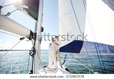 senior couple hugging on sail boat or yacht in sea - stock photo