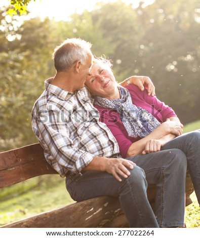 Senior couple in a park sitting on the bench. - stock photo