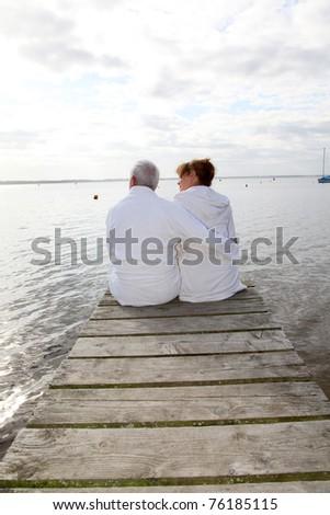 Senior couple in bathrobe sitting on a pontoon - stock photo