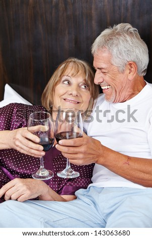 Senior couple in bed celebrating with red wine