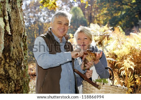 Senior couple in forest holding ceps mushrooms - stock photo