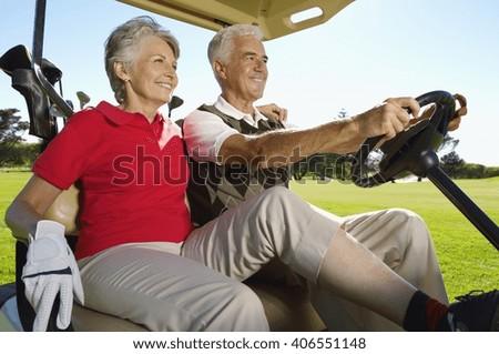 Senior couple in golf car at golf zone - stock photo