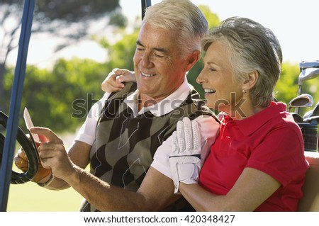 Senior couple in golf car at golf zone
