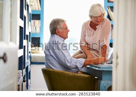 Senior Couple In Home Office Looking At Laptop - stock photo