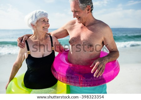 Senior couple in inflatable ring standing on beach on a sunny day - stock photo