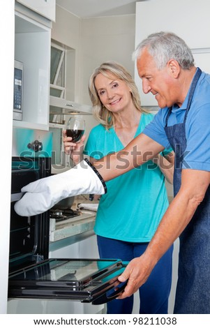Senior couple in kitchen preparing meal together - stock photo
