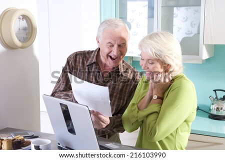 Senior couple in kitchen with laptop computer and paperwork