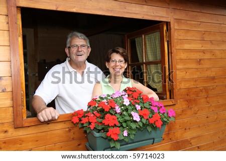 Senior couple in log cabin - stock photo