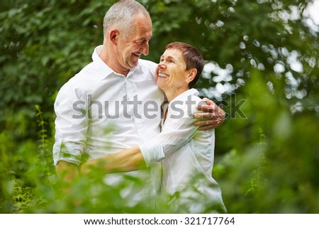 Senior couple in love embracing each other in nature in summer