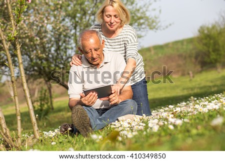 Senior couple in love enjoying togetherness outdoor.They are looking something on tablet.