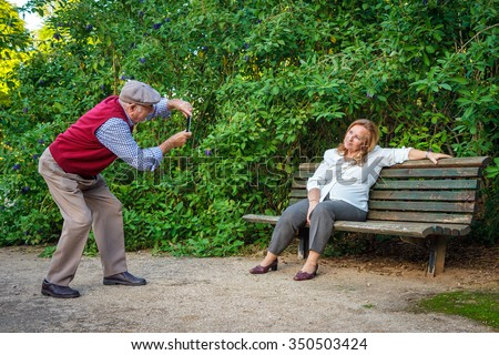 Senior couple in love taking photos in a park. They are 75 years old - stock photo