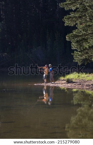 Senior couple, in mid-distance, standing at edge of lake, man fishing, side view - stock photo