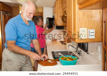Senior couple in prepares a meal together in their RV camper kitchen. - stock photo