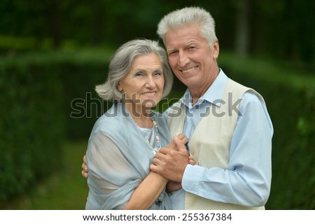 Senior couple in summer park on green background - stock photo