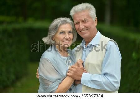 Senior couple in summer park on green background - stock photo