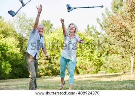 Senior couple in the park playfully throws crutches in the air - stock photo