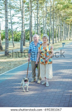 Senior couple in the park with dog on a summer day