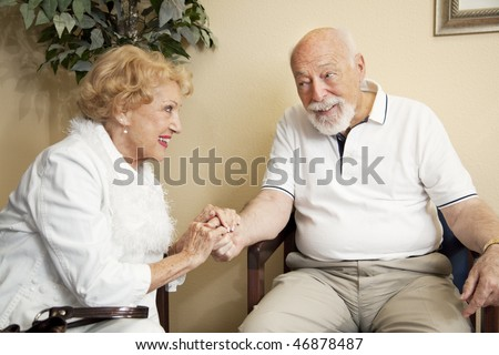 Senior couple in the waiting room of the doctor's office holding hands for moral support.