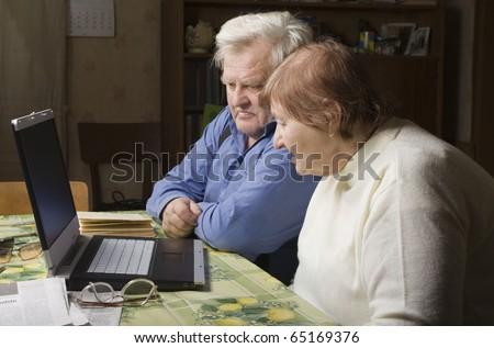Senior Couple in their Dining Room with a Laptop Computer - stock photo