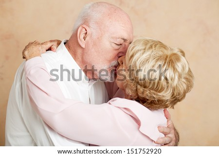 Senior couple in their eighties exchanging a passionate, romantic kiss.   - stock photo