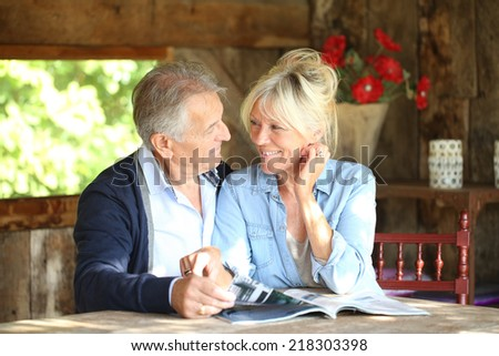 Senior couple in yard reading magazine - stock photo