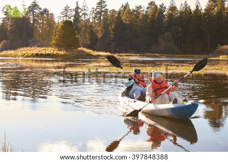 Senior couple kayaking on lake, front view - stock photo