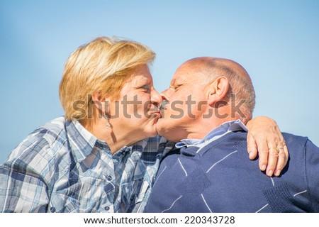 Senior couple kissing outdoors - stock photo