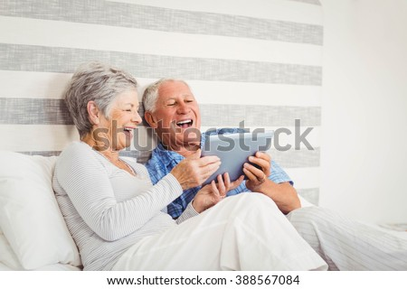 Senior couple laughing while using digital tablet in bedroom - stock photo