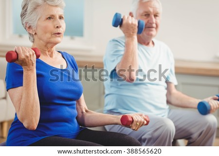 Senior couple lifting dumbbells while sitting on exercise ball at home - stock photo