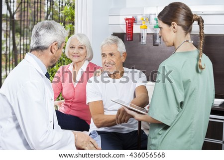 Senior Couple Listening To Doctor While Nurse Holding Digital Ta