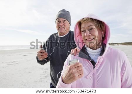 Senior couple listening to music on MP3 player on beach - stock photo