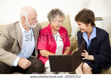 Senior couple listens to a sales pitch in their home.