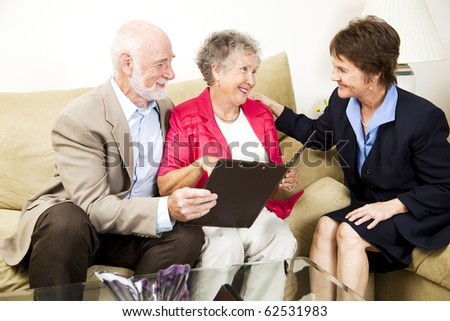 Senior couple listens to a saleswoman or financial consultant in their home.