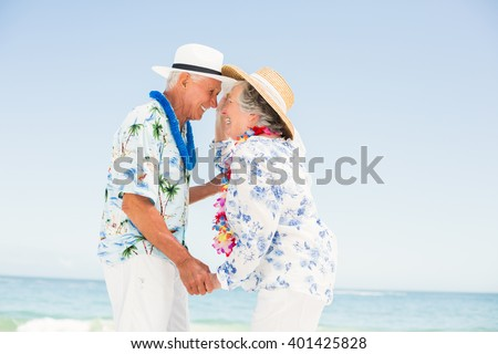 Senior couple looking at each other on the beach on a sunny day - stock photo