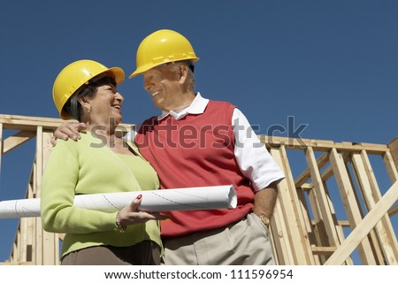 Senior couple looking at each other while standing at construction site - stock photo