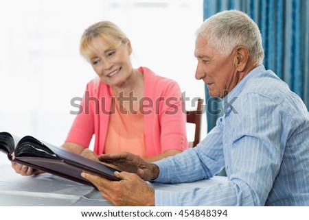 Senior couple looking at photo album in a retirement home
