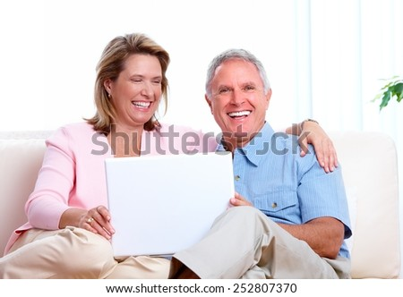 Senior couple looking information at home with computer. - stock photo