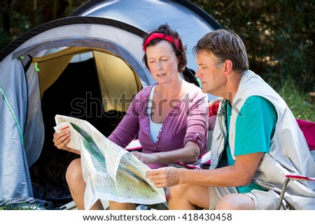senior couple looking the map beside the tent in a forest