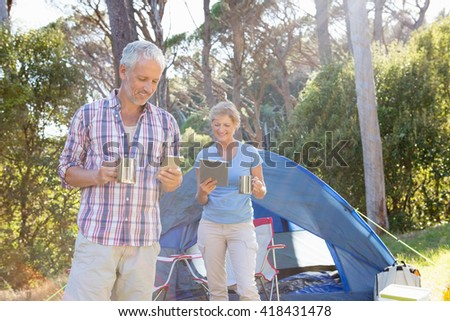 senior couple looking their laptop in a forest - stock photo