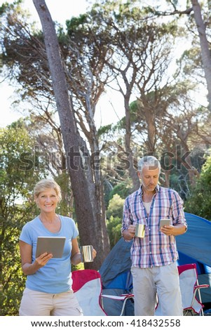 senior couple looking their technology object in a forest - stock photo