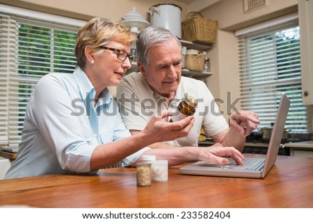 Senior couple looking up medication online at home in the kitchen - stock photo
