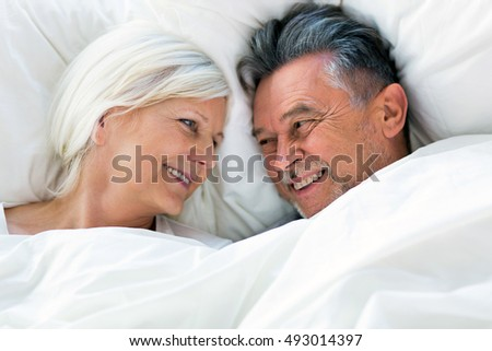 Senior couple lying in bed together